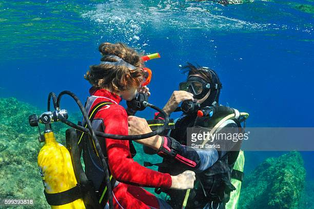 girl (aged 9) with her scuba diving instructor underwater, mediterranean sea, marseille, france, europe - scuba diving stock pictures, royalty-free photos & images