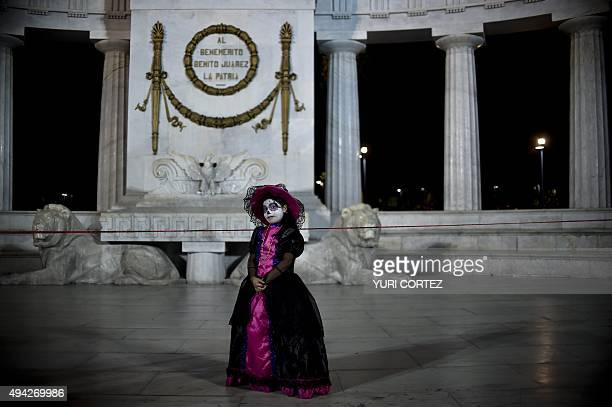 A girl with herr face painted as The Catrina poses at the Benito Juarez monument during the Procession of the Catrinas along Reforma Avenue in Mexico...