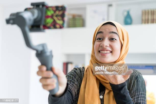 girl with hijab recording video - live streaming stock pictures, royalty-free photos & images