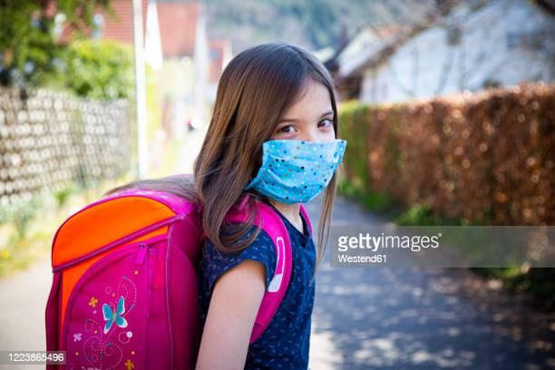 girl with homemade protective mask on her way to school - schulkind nur mädchen stock-fotos und bilder