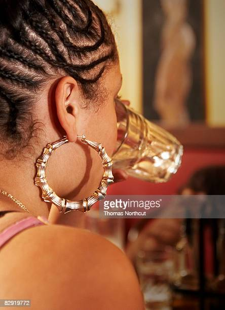 girl with hoop earring drinking water - hoop earring stock pictures, royalty-free photos & images