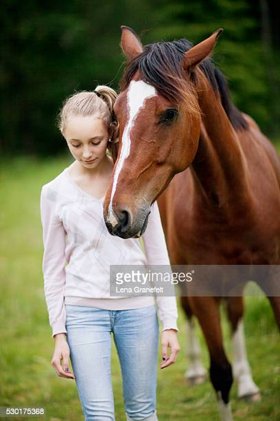 Girl with horse on meadow