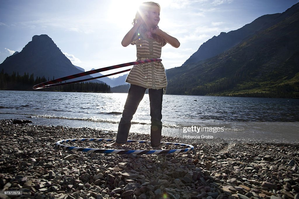 Girl with hula-hoops by lake. : Stock Photo