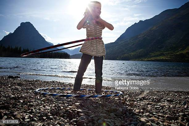 girl with hula-hoops by lake. - two medicine lake montana stock photos and pictures