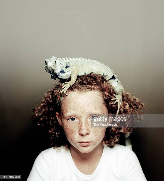 Girl (7-9) with iguana on head