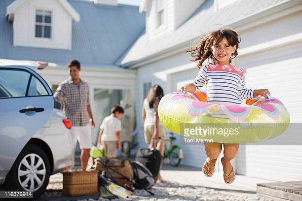 Girl with inflatable ring jumping in driveway