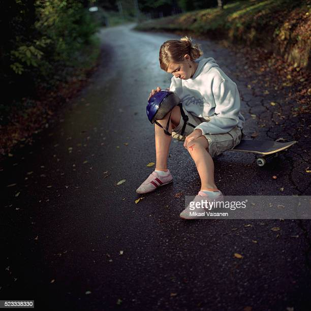 Girl with Injured Knee Sitting on Skateboard
