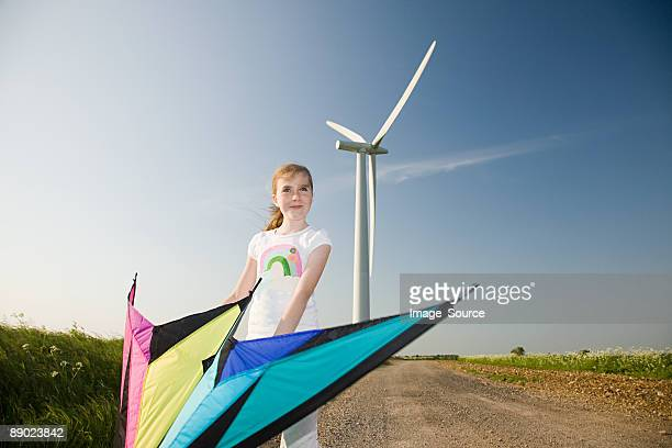 Girl with kite by wind farm