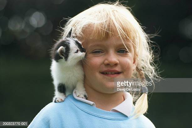 Girl (2-3) with kitten, smiling, close-up