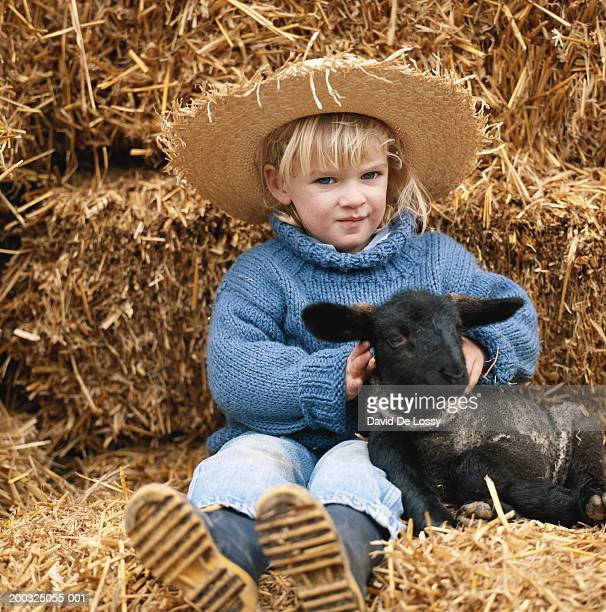 Girl (3-5) with lamb sitting on haystack