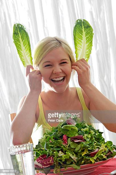 girl with large bowl of lettuce,making rabbit ears - health2010 ストックフォトと画像