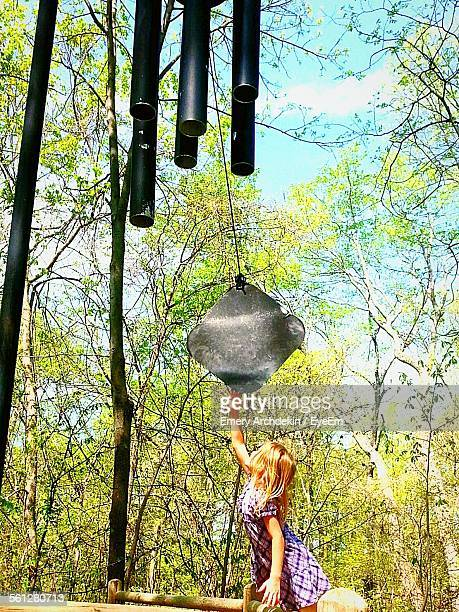 girl with large wind chime against sky in park - emery stock photos and pictures