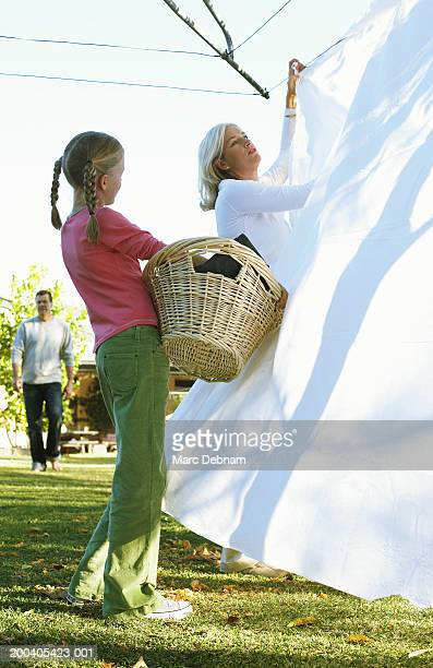 Girl (10-12) with laundry basket watching mother hang out washing