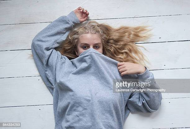 Girl with long blonde hair lying on painted floor