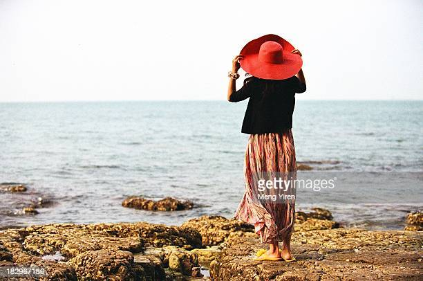A girl with long dress standing beside the sea