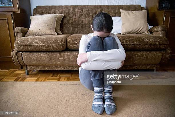 girl with lower head on her knee sitting beside bed