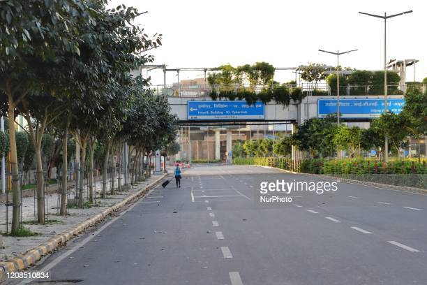 Girl with luggage walks on a deserted road in Gurugram on the outskirts of New Delhi, India on 29 March 2020. To combat the spread of deadly...