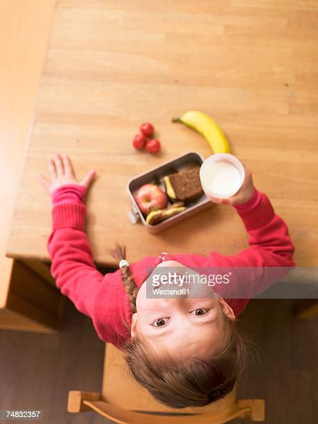 Girl (4-7) with lunch box on desk, holding glass of milk, overhead view, portrait