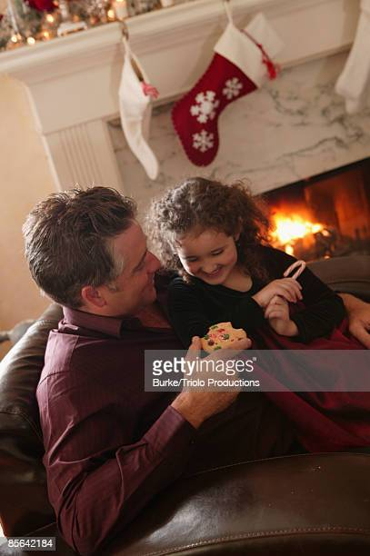 girl with man eating christmas cookie and candy cane - mint plant family stock pictures, royalty-free photos & images