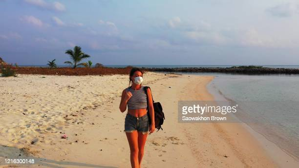 girl with mask on face for protecting by coronavirus, walking on empty beach alone at sunset with purple cloudy sky in thailand - face guard sport stock pictures, royalty-free photos & images