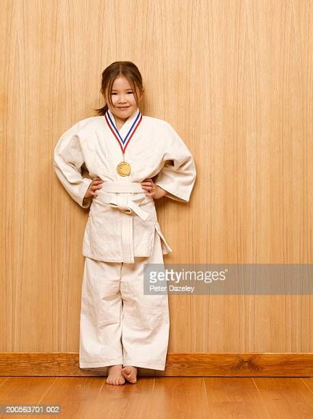 Girl (6-7) with medal in judo kit, portrait