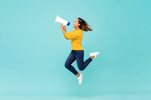 Girl with megaphone jumping and shouting 1166716628
