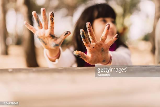 girl with messy hands at picnic table in park - somente crianças imagens e fotografias de stock