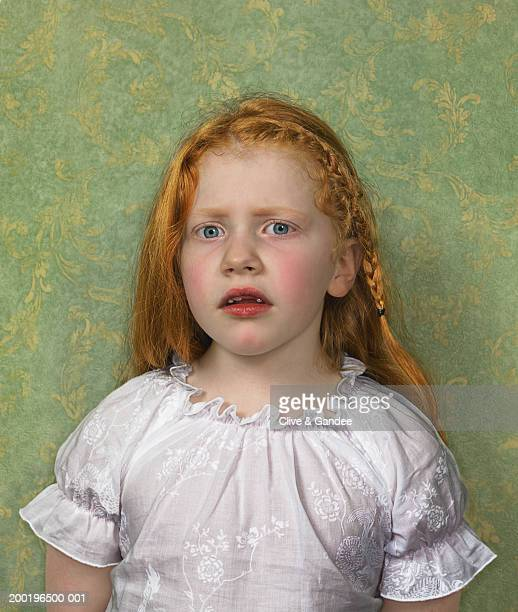 Girl (6-8) with missing front tooth, portrait
