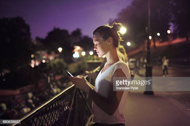 Girl with mobile device on street at night