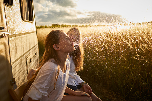 Girl with mother at caravan spitting water - gettyimageskorea