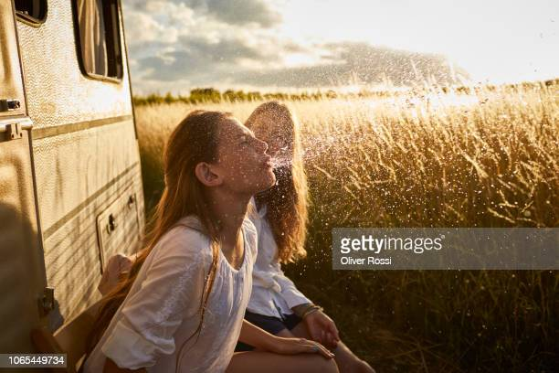 girl with mother at caravan spitting water - sorglos stock-fotos und bilder