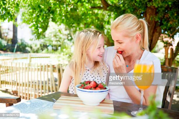 Girl with mother eating stawberries