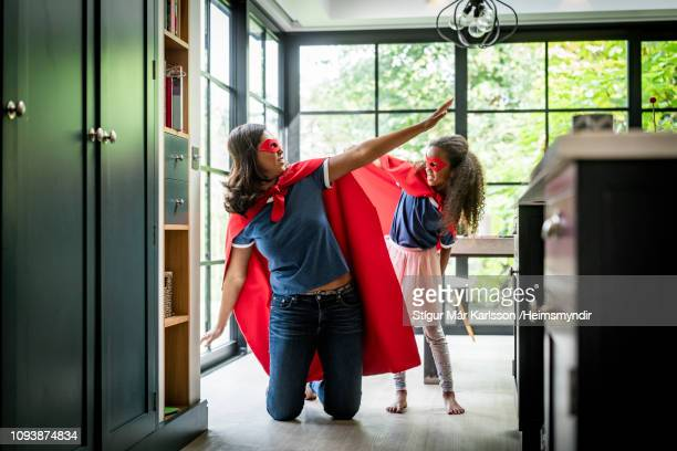 girl with mother in red superhero costume at home - superhero stock pictures, royalty-free photos & images