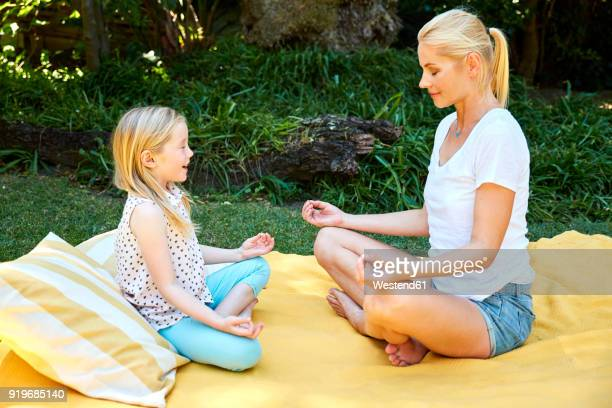 Girl with mother practicing yoga on a blanket