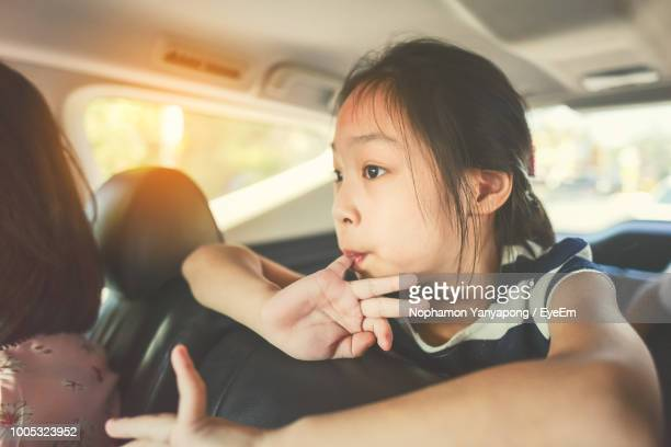 girl with mother sitting in car - family inside car stock photos and pictures