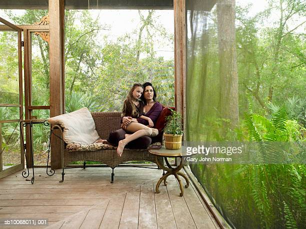 Girl (6-7) with mother sitting on porch