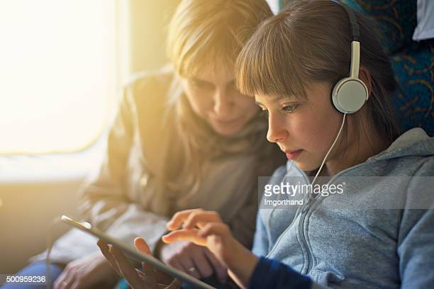 Girl with mother travelling on train and playing on tablet