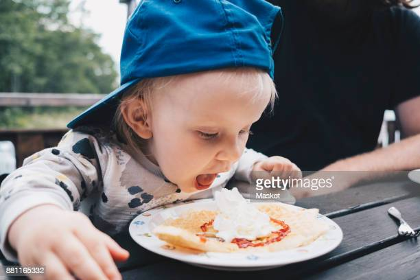 Girl with mouth open looking at food while sitting by father at table