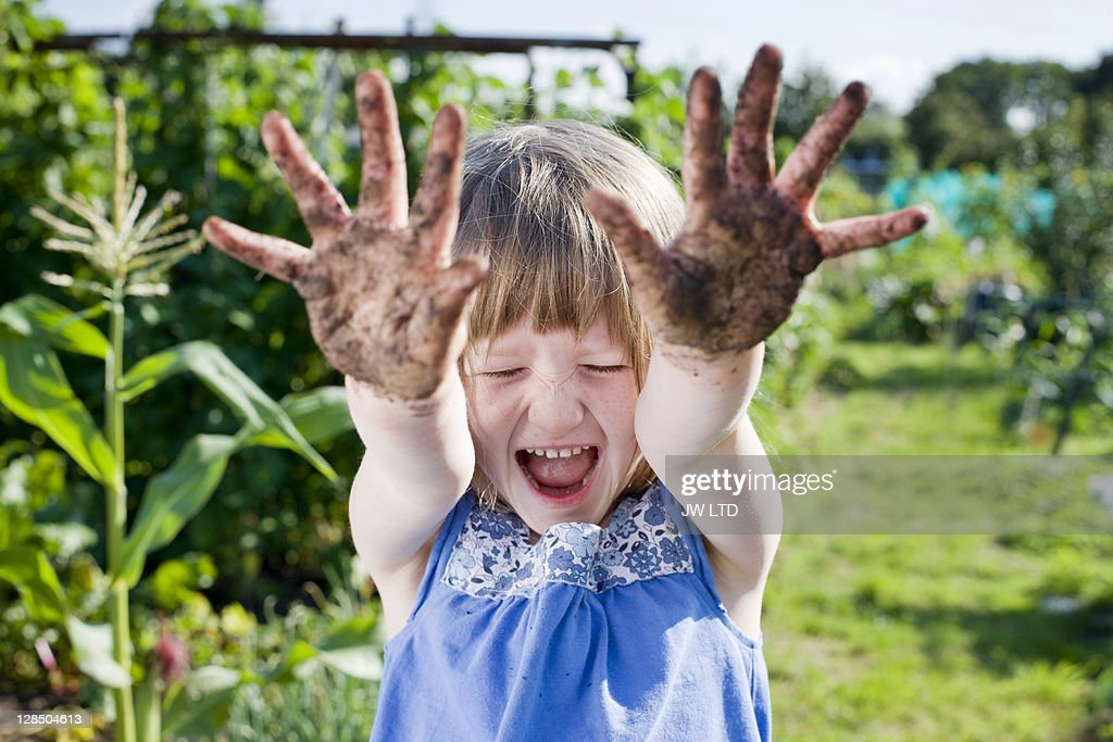 Girl with muddy hands : Stock Photo