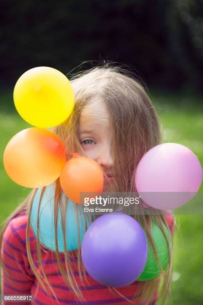 Girl with multi colored balloons stuck in her hair