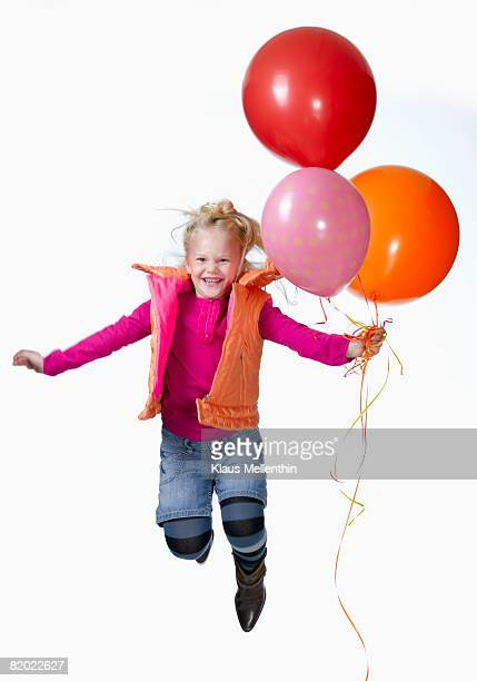 Girl (8-9) holding balloons and jumping, portrait