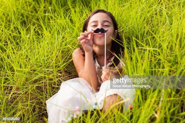 Girl with mustache prop having fun outdoor.