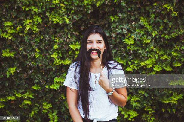 Girl with mustache prop on her face.