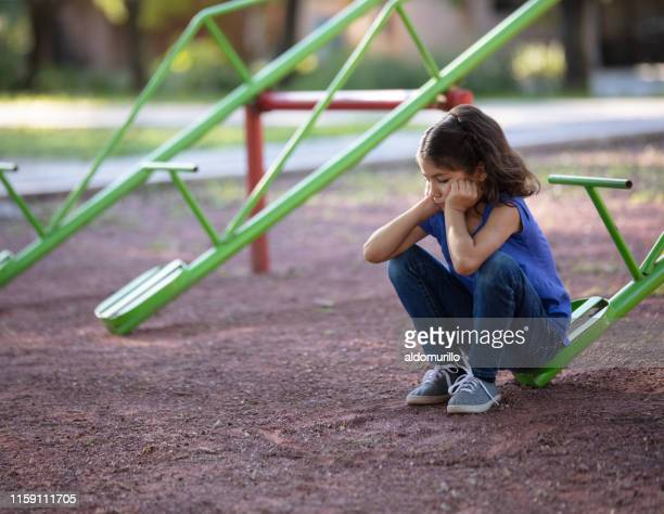 girl with no one to play with on the teeter totter - bullying stock pictures, royalty-free photos & images