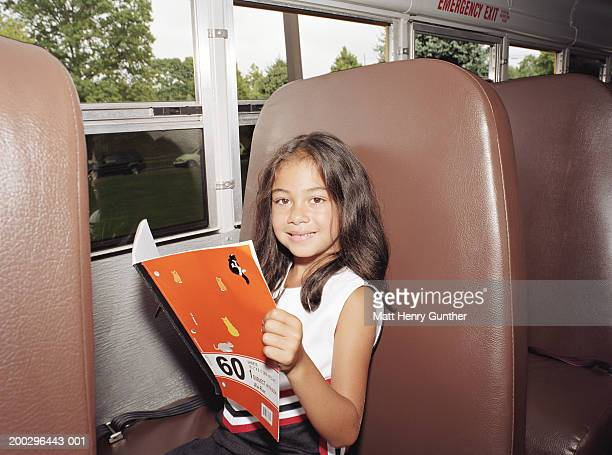 Girl (6-8) with notebook in schoolbus smiling, portrait