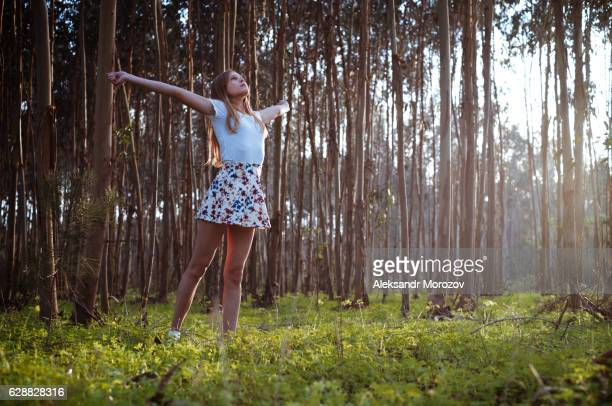 a girl with open arms is standing on a clearing in the forest - minirok stockfoto's en -beelden