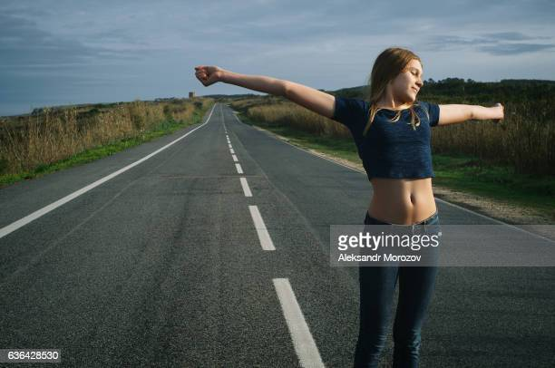 A girl with open arms is standing on the background of an empty road