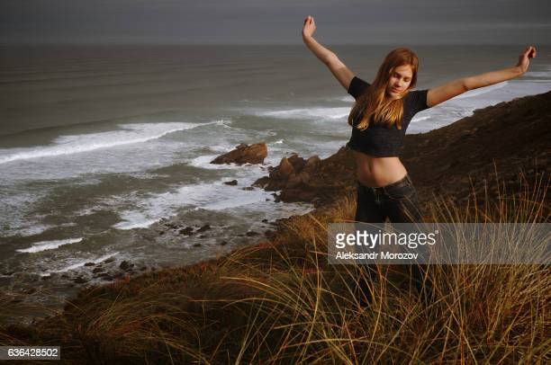 Girl with open arms stands on the background of the ocean