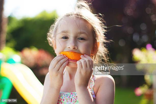 girl with orange slice in mouth