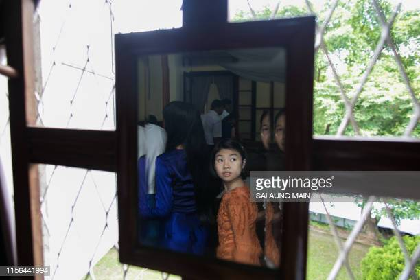 TOPSHOT A girl with other visitors is reflected on a mirror at the General Aung San Museum former residence of Aung San Suu Kyi's father during the...